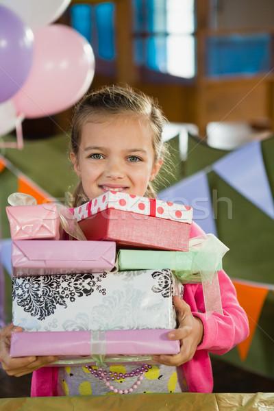 Birthday girl holding various gift boxes at home Stock photo © wavebreak_media