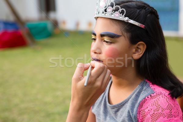 Cropped hand doing face paint on girl Stock photo © wavebreak_media