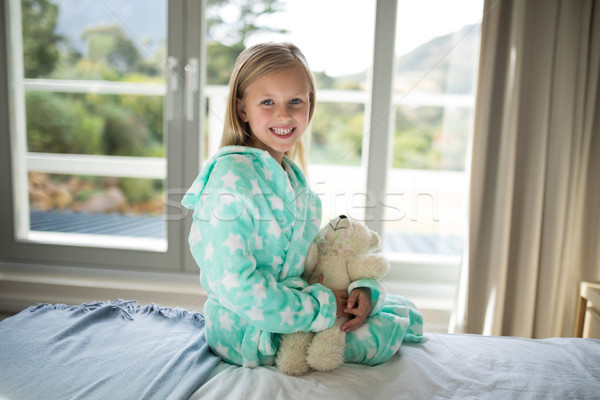 Smiling girl holding teddy bear on bed in bedroom Stock photo © wavebreak_media