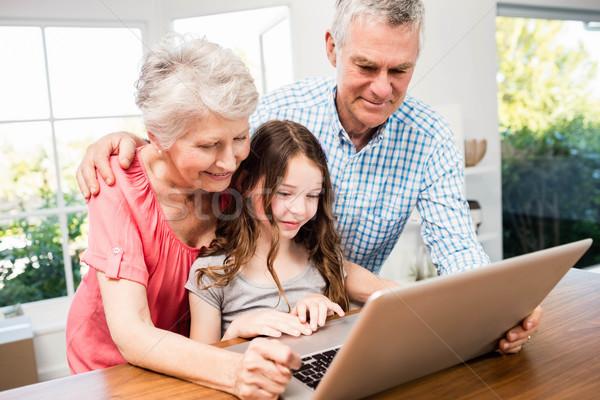 Portrait of smiling grandparents and granddaughter using laptop Stock photo © wavebreak_media