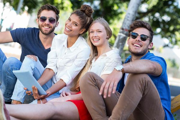 Hip friends holding tablet and sitting on sidewalk Stock photo © wavebreak_media