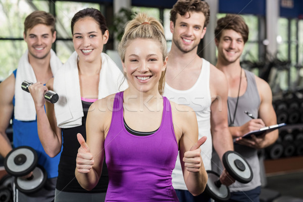 Fitness group lifting dumbbells and showing thumbs up Stock photo © wavebreak_media