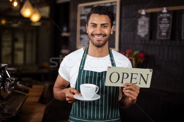 Smiling barista holding coffee and open sign Stock photo © wavebreak_media