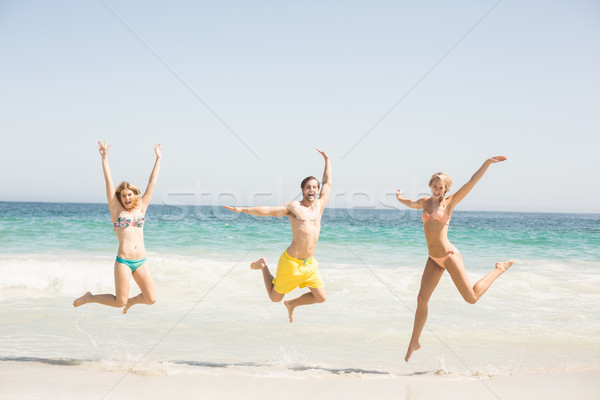 Stock photo: Happy young friends jumping on the beach
