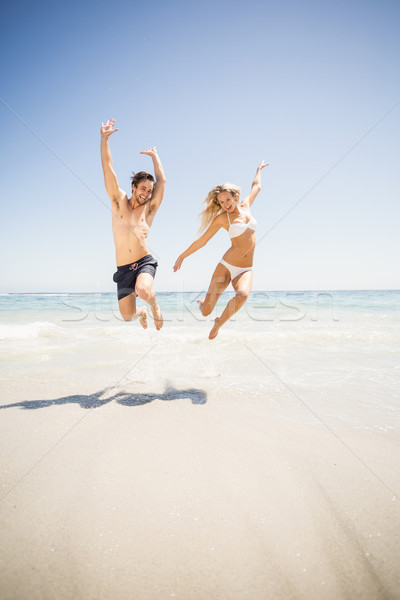 Stock photo: Happy couple jumping on the beach