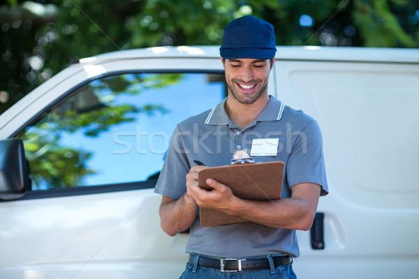 Sorridente entrega pessoa escrita clipboard em pé Foto stock © wavebreak_media