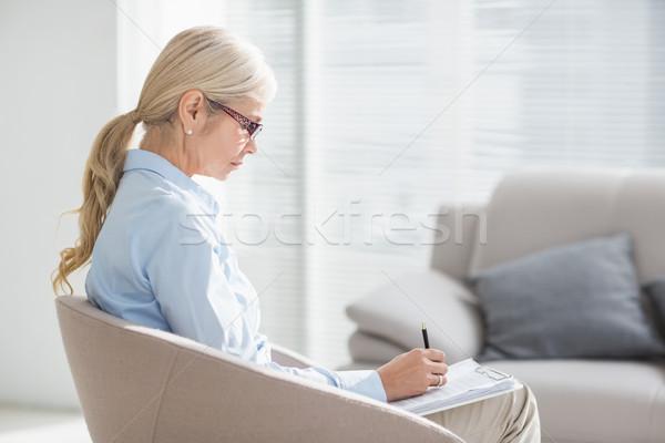 Terapeuta escrita notas sofá escritório Foto stock © wavebreak_media