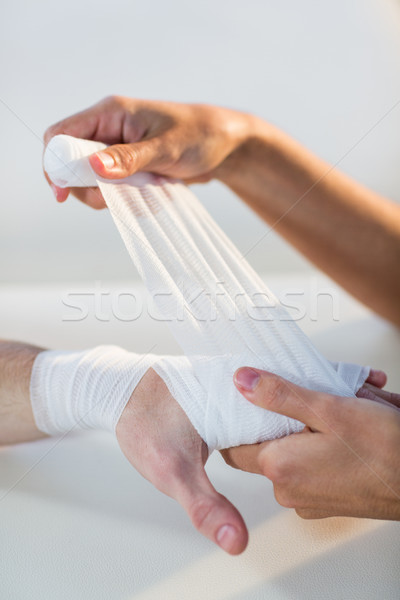 Physiotherapist putting bandage on male patient hand Stock photo © wavebreak_media