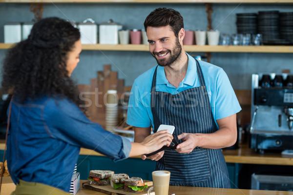 Femme payer Bill smartphone technologie café Photo stock © wavebreak_media