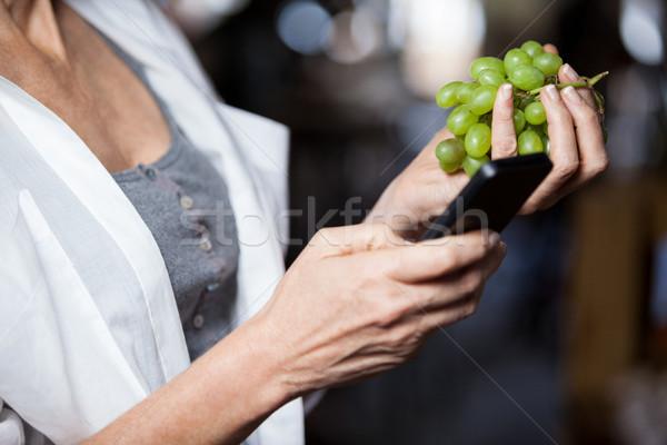 Stock fotó: Középső · rész · női · tart · szőlő · mobiltelefon · áruház
