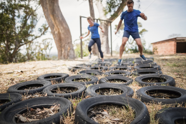 Man and woman running over the tyre during obstacle course Stock photo © wavebreak_media