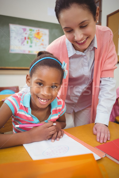 Stock photo: Pupil and teacher at desk in classroom