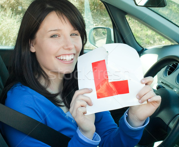 Happy teen girl sitting in her car tearing a L-sign Stock photo © wavebreak_media