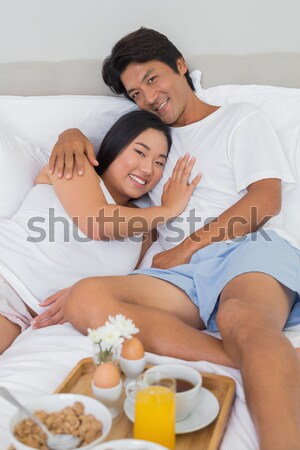 Cheerful lovers eating cereals lying in the bed Stock photo © wavebreak_media