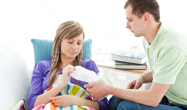 Young man with tissues and his sick girlfriend lying on a sofa Stock photo © wavebreak_media