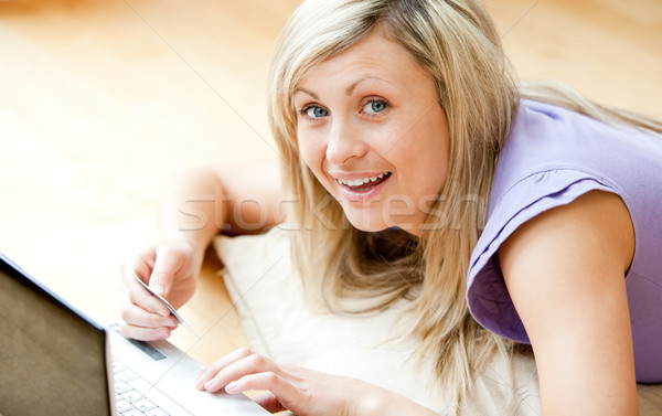 Cheerful woman shopping on-line lying on a sofa at home Stock photo © wavebreak_media