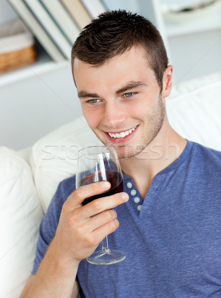 Animated young man drinking wine sitting on the sofa in the living-room Stock photo © wavebreak_media