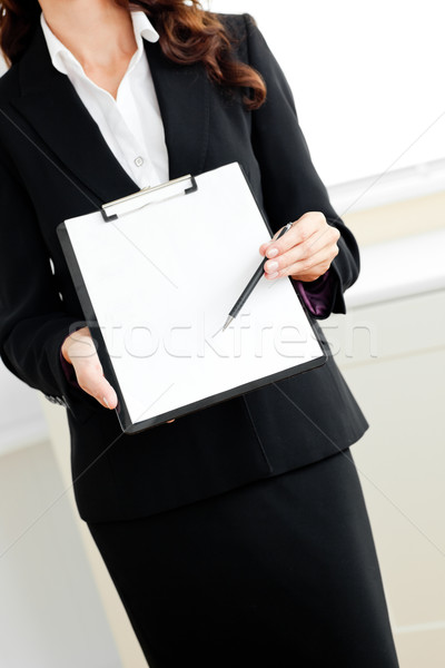 Close-up of an assertive businesswoman taking notes on her clipboard against a white background Stock photo © wavebreak_media