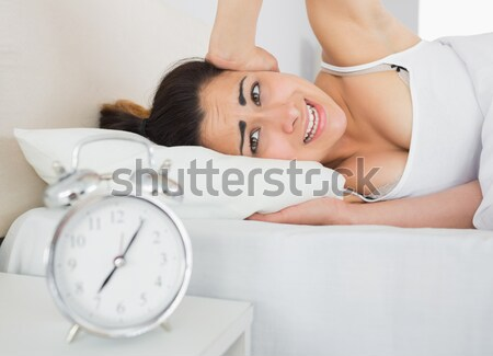 Unhappy man looking at his alarm clock while lying on his bed at home Stock photo © wavebreak_media