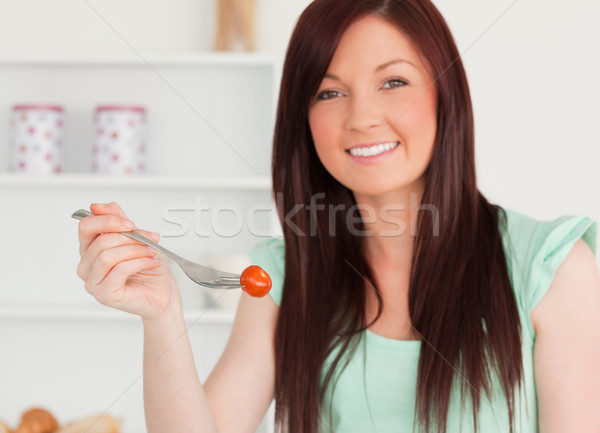 Good looking red-haired woman cutting eating a cherry tomato in the kitchen in her appartment Stock photo © wavebreak_media