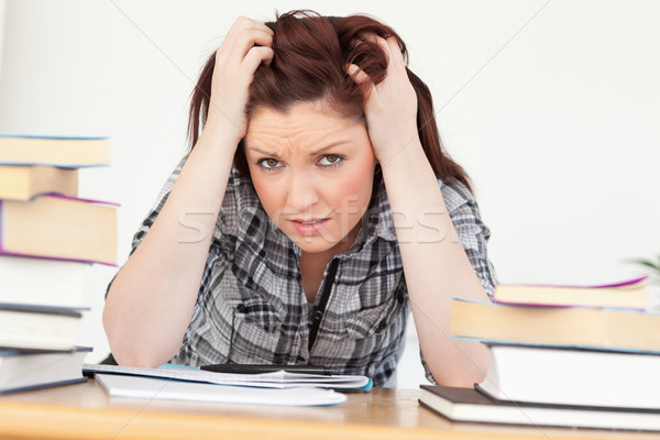 Beautiful red-haired female being upset while studying for an examination at her desk Stock photo © wavebreak_media