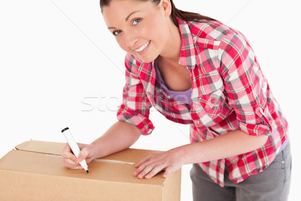 Portrait of an attractive woman writing on cardboard boxes with a marker while standing against a wh Stock photo © wavebreak_media