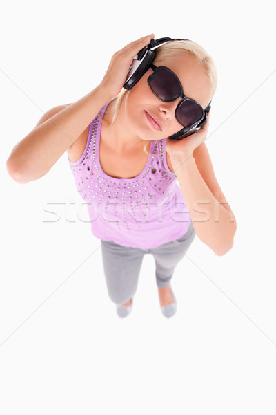 Glorious lady with sunglasses and earphones in a studio Stock photo © wavebreak_media