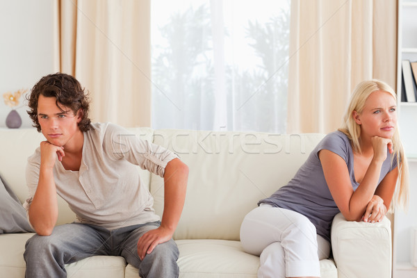 Upset couple sitting on a couch with their hand on their chin Stock photo © wavebreak_media