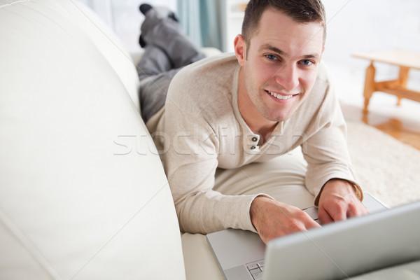Boa aparência homem sofá laptop olhando câmera Foto stock © wavebreak_media