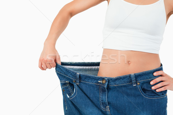 Fit woman wearing too large jeans against a white background Stock photo © wavebreak_media