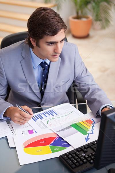 Young businessman analyzing statistics at his desk Stock photo © wavebreak_media