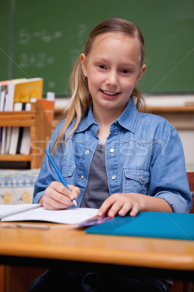 Portrait of a smiling schoolgirl writing in a classroom Stock photo © wavebreak_media