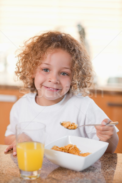 Happy smiling girl eating cereals for breakfast Stock photo © wavebreak_media