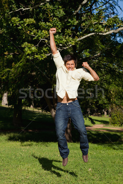 Man jumping off the ground while raising his arms while he is rejoicing in the park Stock photo © wavebreak_media