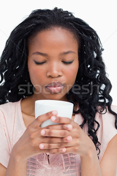 A young woman has her eyes closed and is smelling coffee out of a cup she is holding Stock photo © wavebreak_media