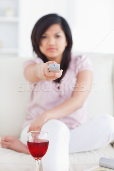Woman holding a television remote in front of a glass of wine in a living room Stock photo © wavebreak_media