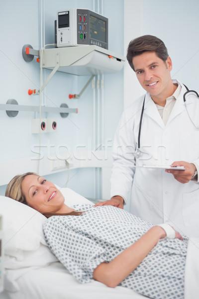 Doctor and patient smiling in hospital ward Stock photo © wavebreak_media