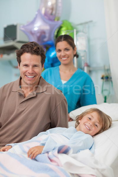 Child lying on a medical bed next to his father in hospital ward Stock photo © wavebreak_media