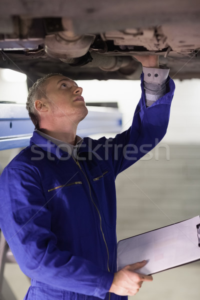 Mechanic touching the below of a car while holding a clipboard in a garage Stock photo © wavebreak_media