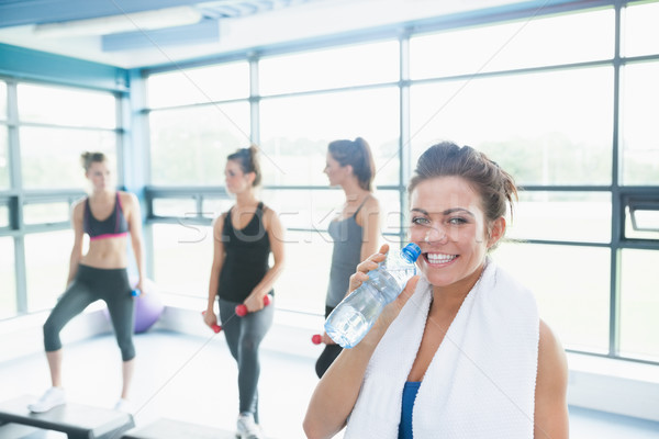 Stock photo: Woman with bottle of water in aerobics class in gym