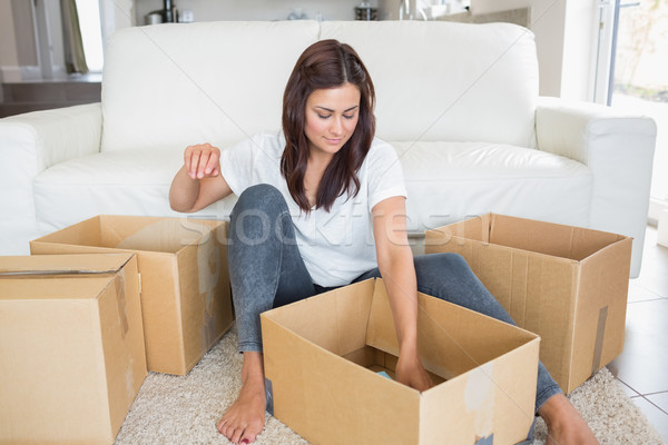Woman looking into moving boxes in the living room Stock photo © wavebreak_media