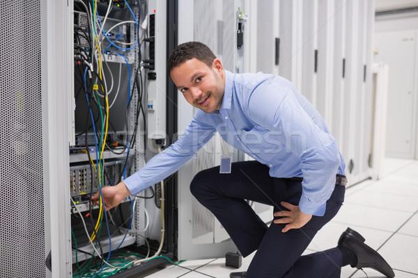 Technician plugging cable into server in data center Stock photo © wavebreak_media
