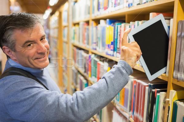 Mosolyog férfi elvesz táblagép polcok könyvtár Stock fotó © wavebreak_media