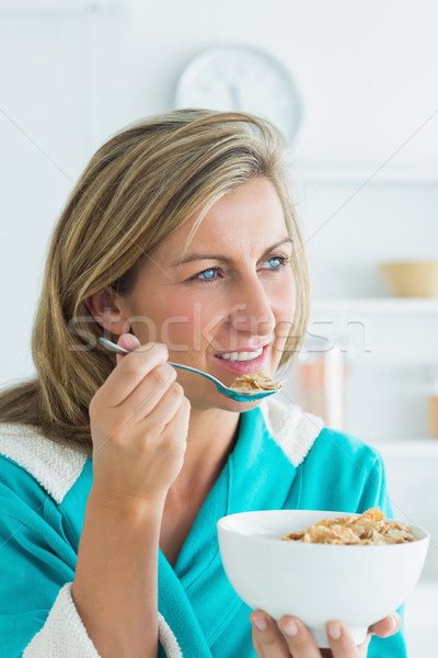 Smiling woman eating cereal in kitchen Stock photo © wavebreak_media