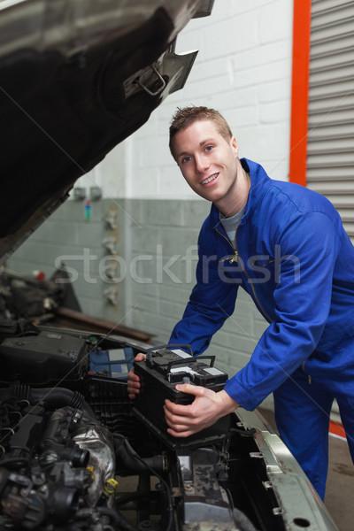 Happy mechanic with battery by car Stock photo © wavebreak_media