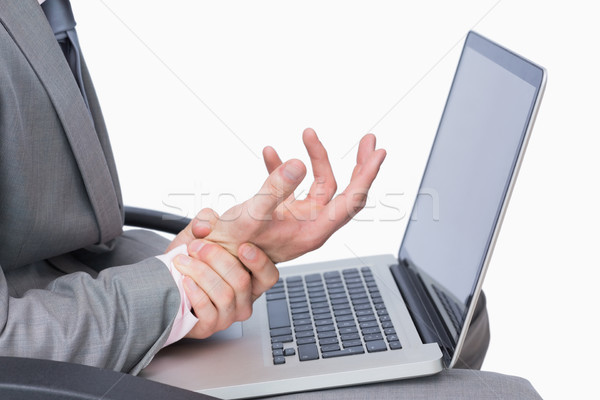 Uomo d'affari polso dolore utilizzando il computer portatile primo piano bianco Foto d'archivio © wavebreak_media