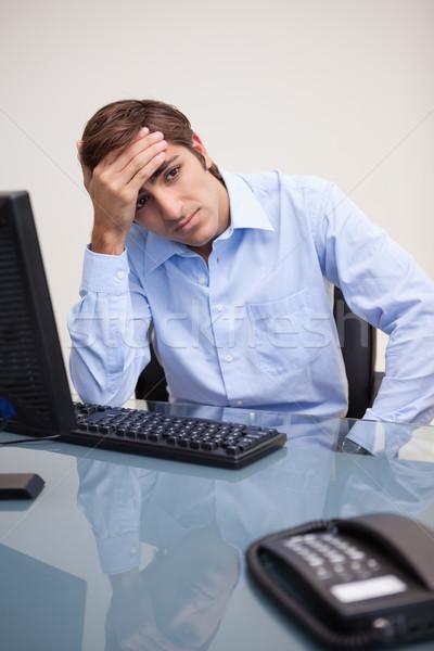 Jovem tenso homem de negócios sessão mesa de escritório cabeça Foto stock © wavebreak_media