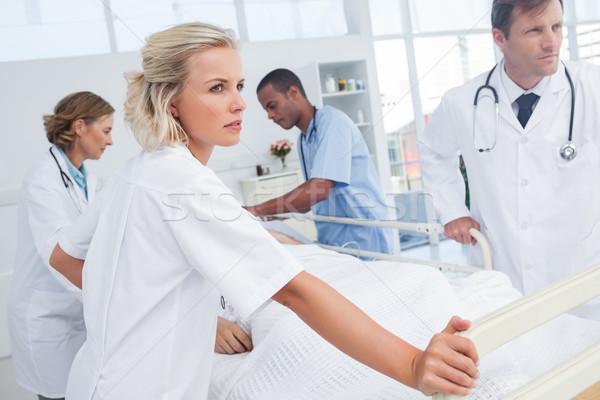 Stockfoto: Ernstig · artsen · lopen · patiënt · bed · vrouw