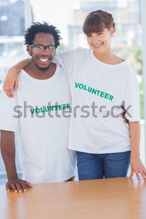 Sonriendo voluntarios manos junto blanco equipo Foto stock © wavebreak_media