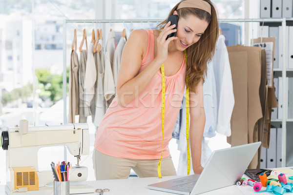 Fashion designer using laptop and cellphone in studio Stock photo © wavebreak_media